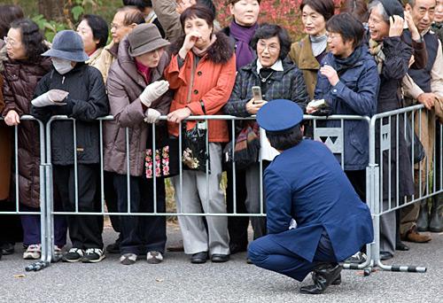 Halkın görüş açısını kapatmamak için çömelerek görev yapan polis.