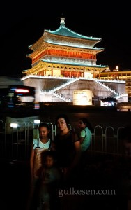 Gece Çan Kulesi ve önünde poz veren bir aile.
