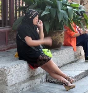 Caminin bahçesinde telefon muhabbeti yapan bir müslüman kadın.