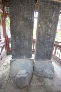 Bahçede, kaplumbağa (bixi) üzerine yerleştirilmiş yazıtlar. Çin mitolojisinde Ejderha Kral'ın dokuz oğlundan birisi olan bixi, Orhun yazıtlarında da kaide olarak kullanılmış.